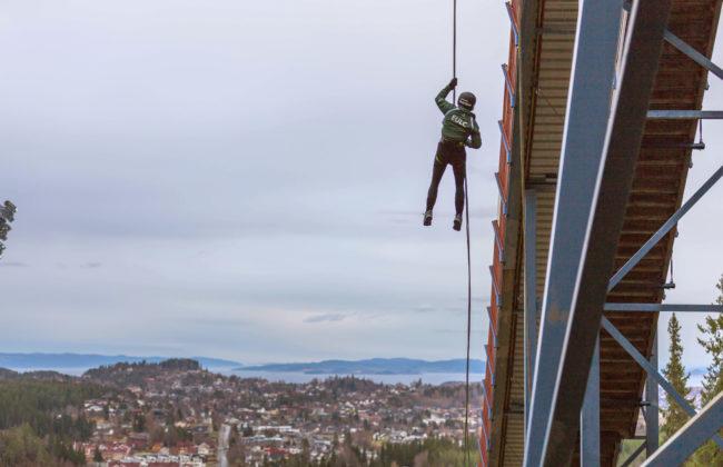 Person in helmet hanging from bridge overlooking homes and sea